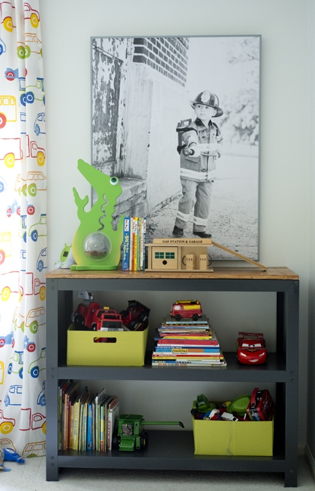 Poster print of fireman in kids room with kids bookshelf underneath