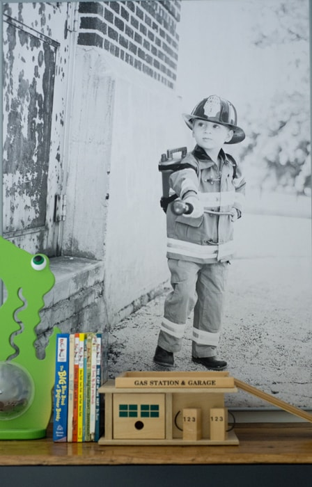 Kid dressed up in fireman costume poster print