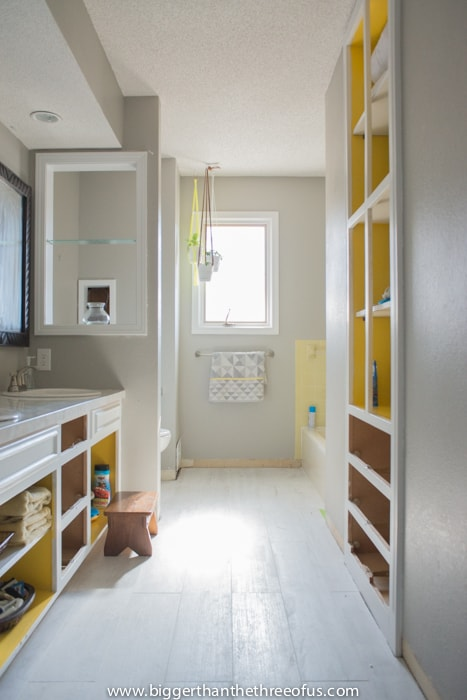 Hallway bathroom in progress with gray walls and white cabinets