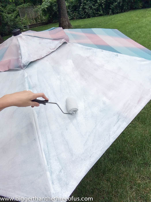 Painting an outdoor umbrella with a roller