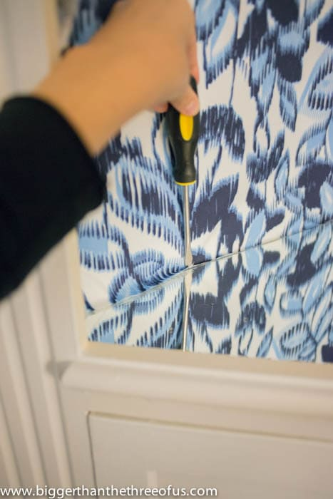 Use a screwdriver to push the fabric down
