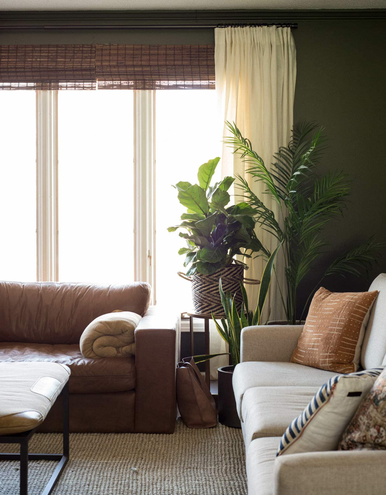 Bamboo blinds on window with white curtains over