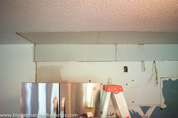 showing sheetrock installed above fridge