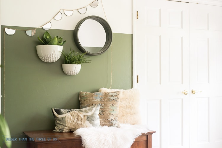 Wall planters and mirrors on a half-painted wall