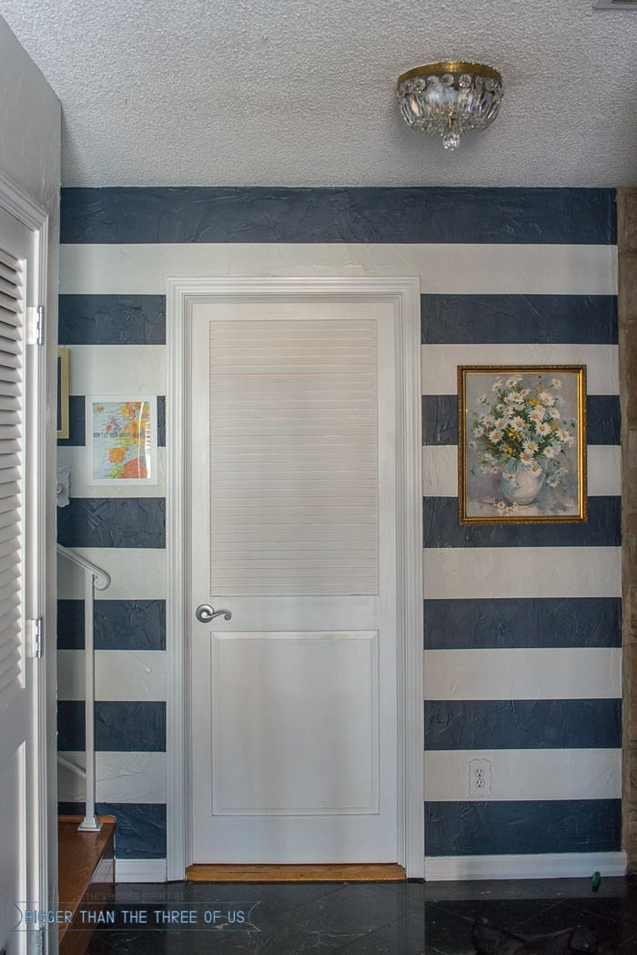 Blue and white stripe wall with frames