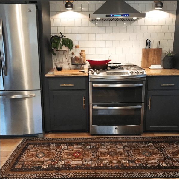 Homestead Seattle Vintage Persian Rug in Kitchen with Dark Kitchen cabinets, white tile and sconces flanking the stove