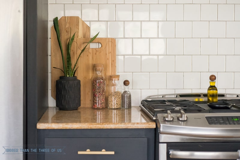 Black kitchen with granite and gold brass pull