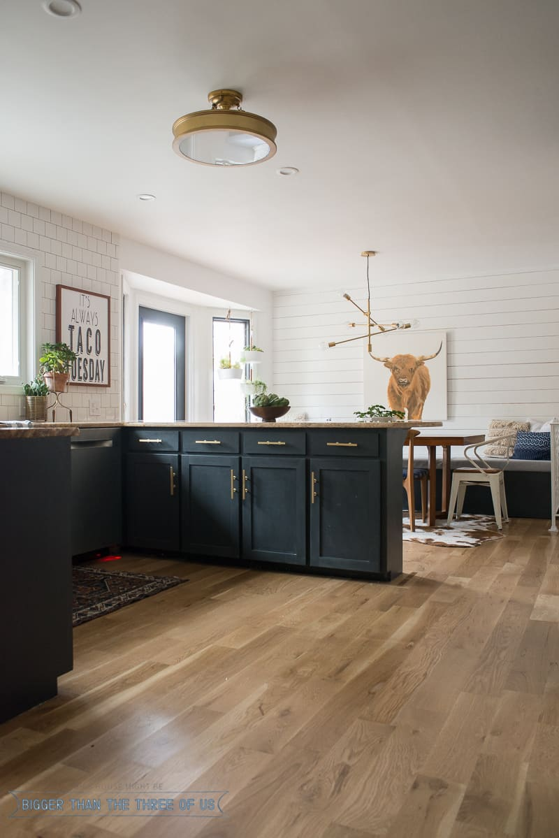 Dark blue kitchen with brass bar pulls and wood accents