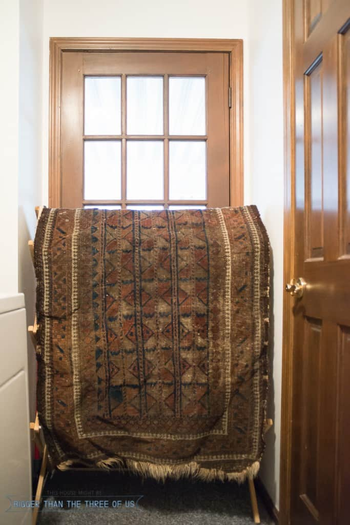 clean a vintage rug and dry it over a drying rack