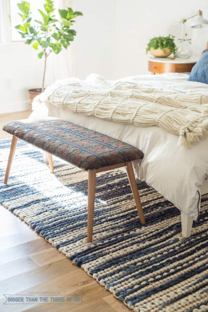 Add texture to your room by upholstering a plain bench with a vintage distressed rug.