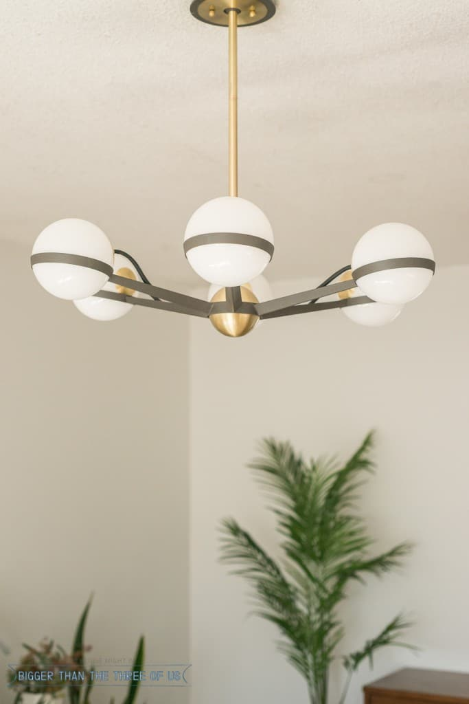 Amazing brass and steel light in mid-century bedroom design.