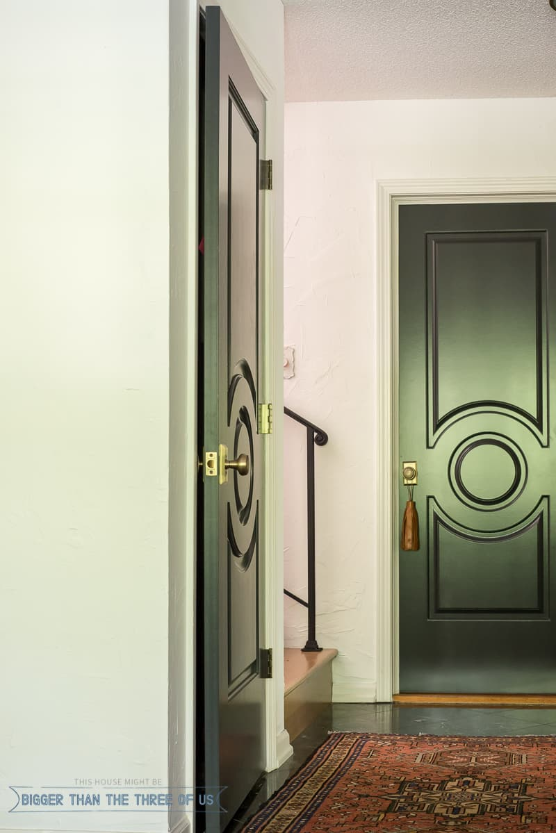 Dark interior doors with marble flooring and a vintage rug