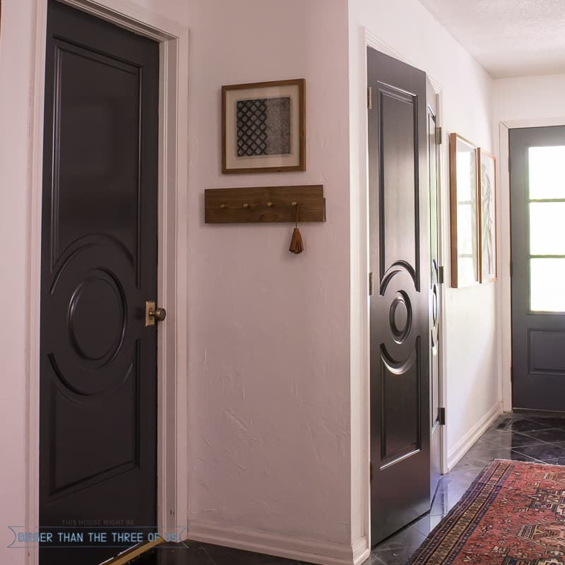 Entryway with dark doors, marble flooring, white walls and black and white accents