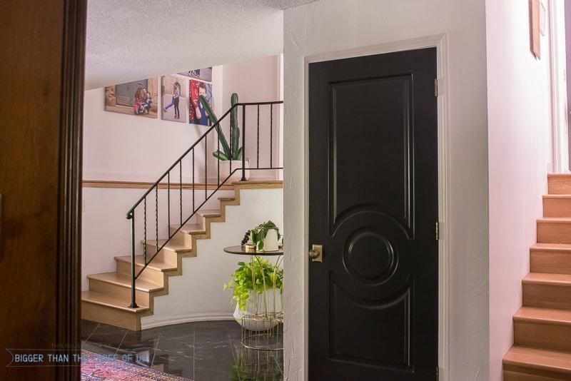 Modern Entryway with marble flooring, black doors and a vintage rug