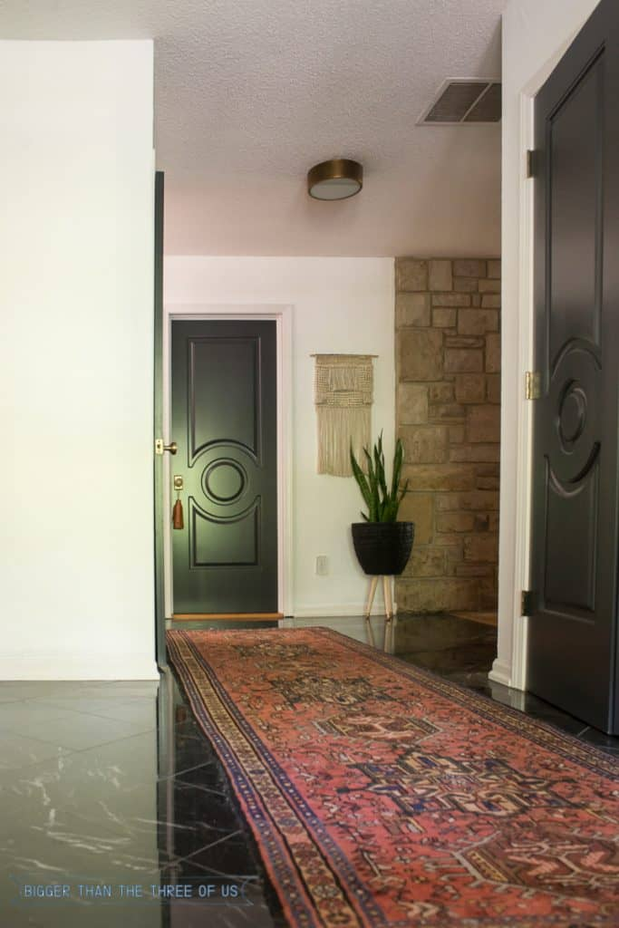 Vintage runner in entryway with black doors