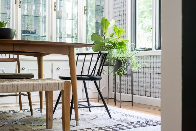 Mid-Century Dining Room with black chairs, tall planters and vintage rug