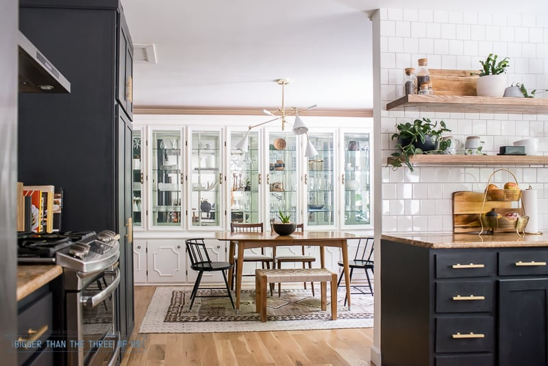 Navy and White kitchen with open shelving open to the dining room with mid-century furniture