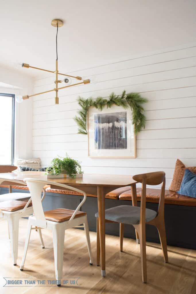 Garland over art hanging in dining room. Modern shiplap walls in Christmas Home Tour.