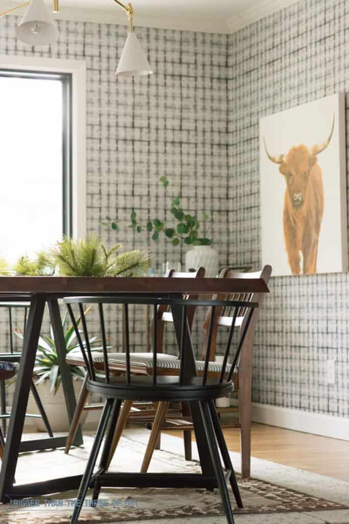 Wallpaper in dining room with midcentury furniture and a highland cow painting.