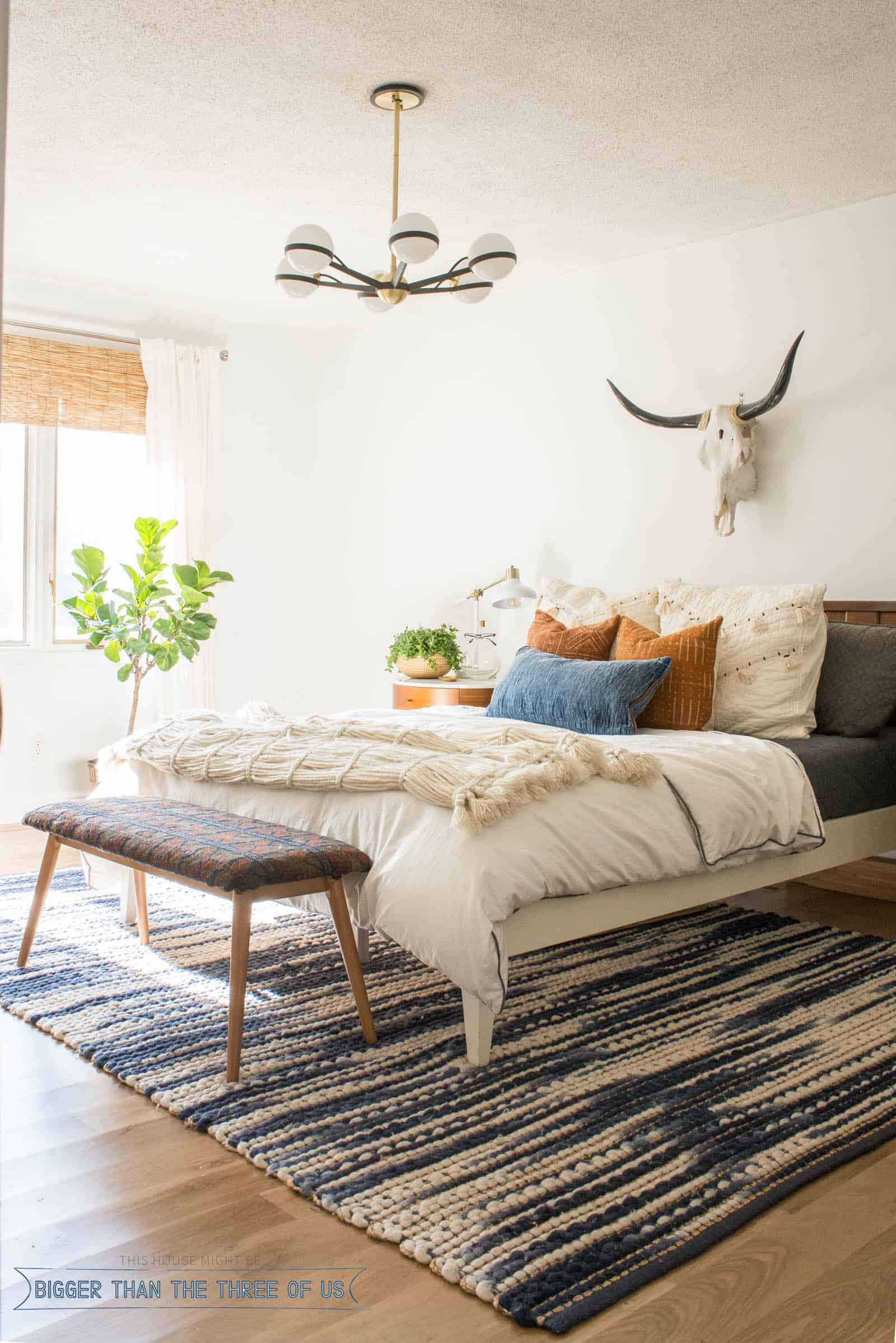 Midcentury bedroom with white walls, a DIY rug bench, blue and white rug and wood flooring. | DIY OR NOT