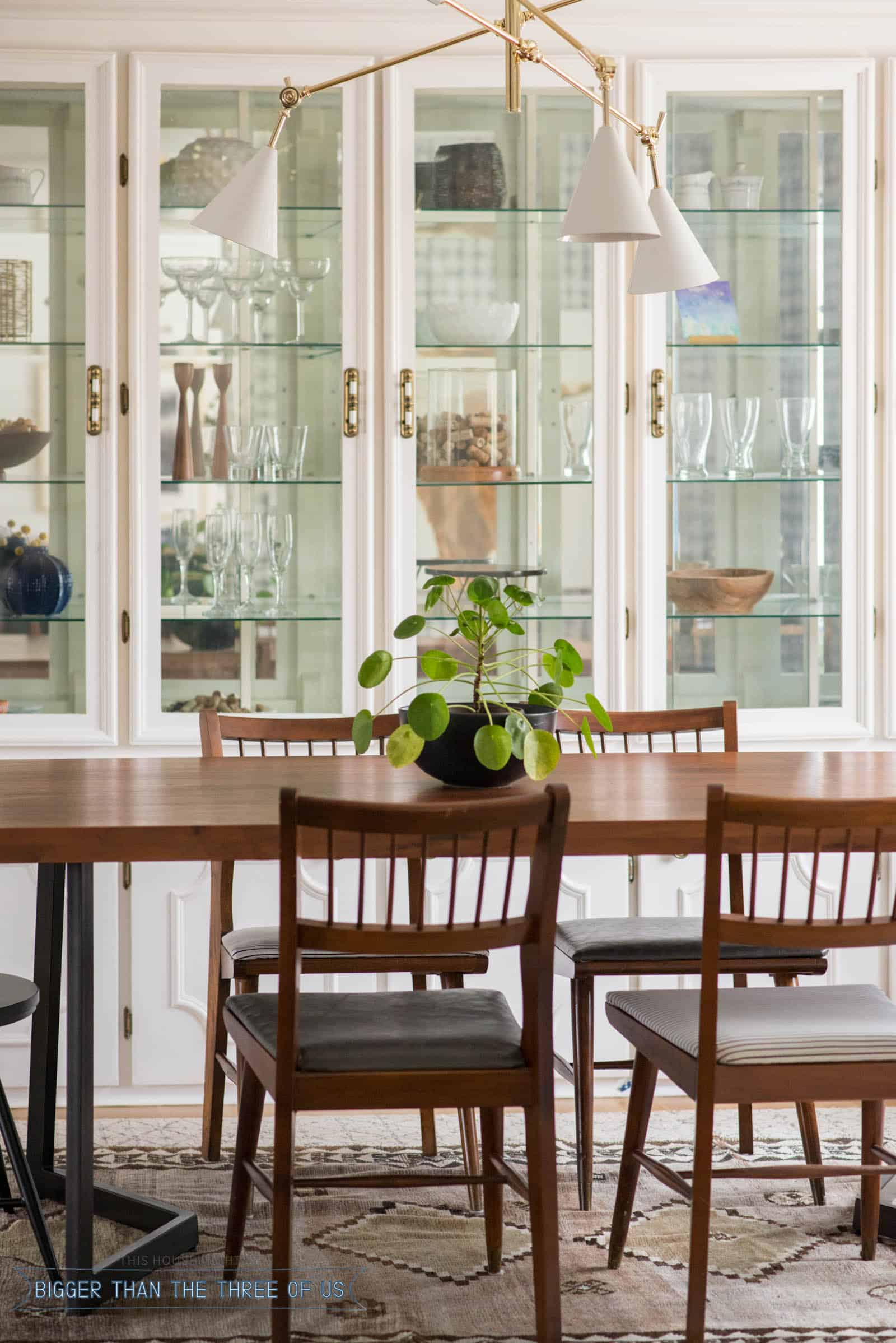 Leather upholstered midcentury chairs with black spindle chairs in dining room
