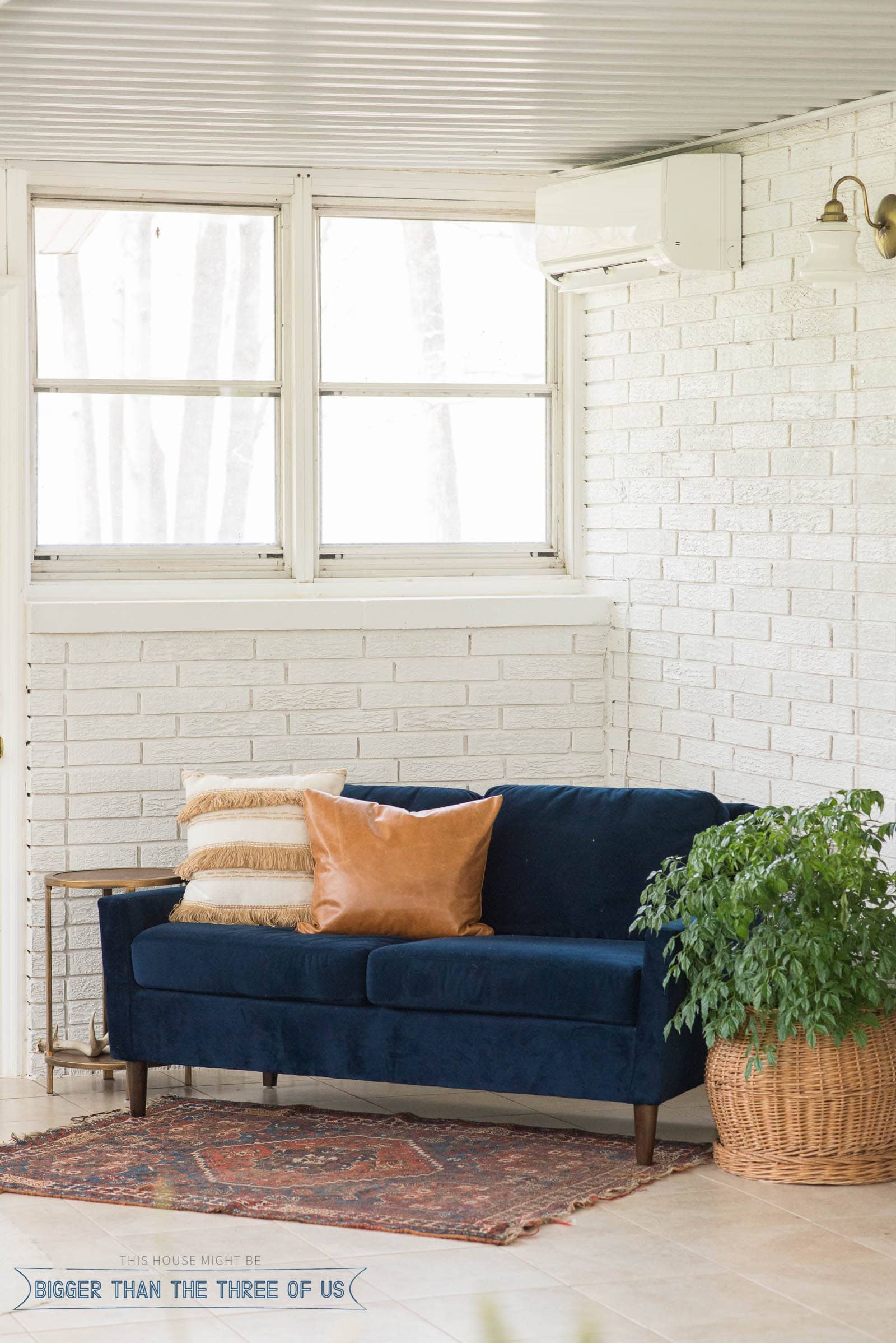 White painted brick in sunroom with a mini split.