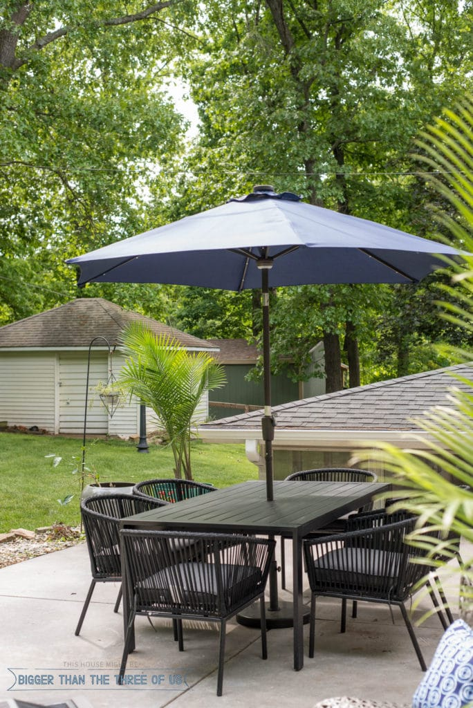 Outdoor patio space with modern black table and blue umbrella