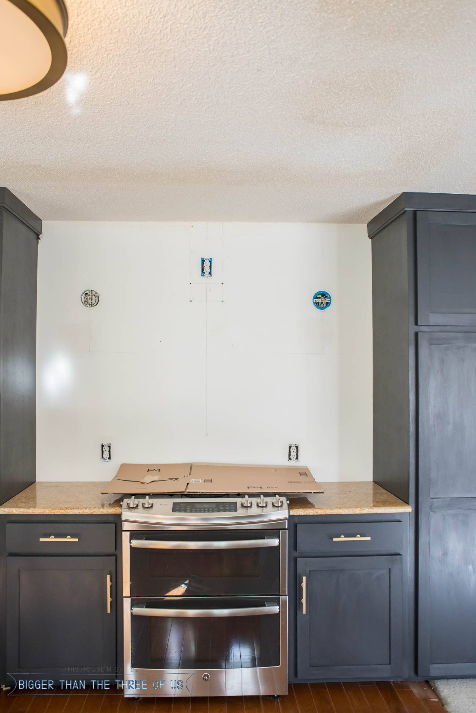 Sconces on each side of oven in modern kitchen.
