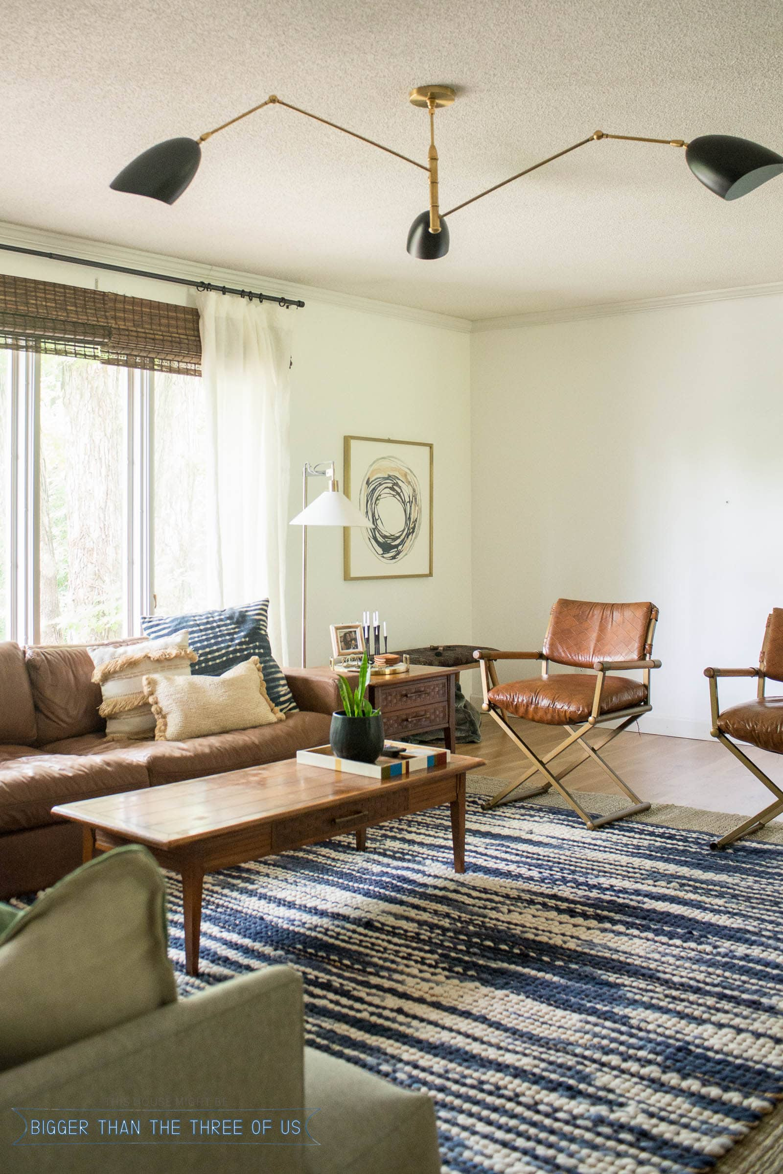 Couch in front of windows in living room. Brown leather couch with blue and white rug and mid-century furniture.