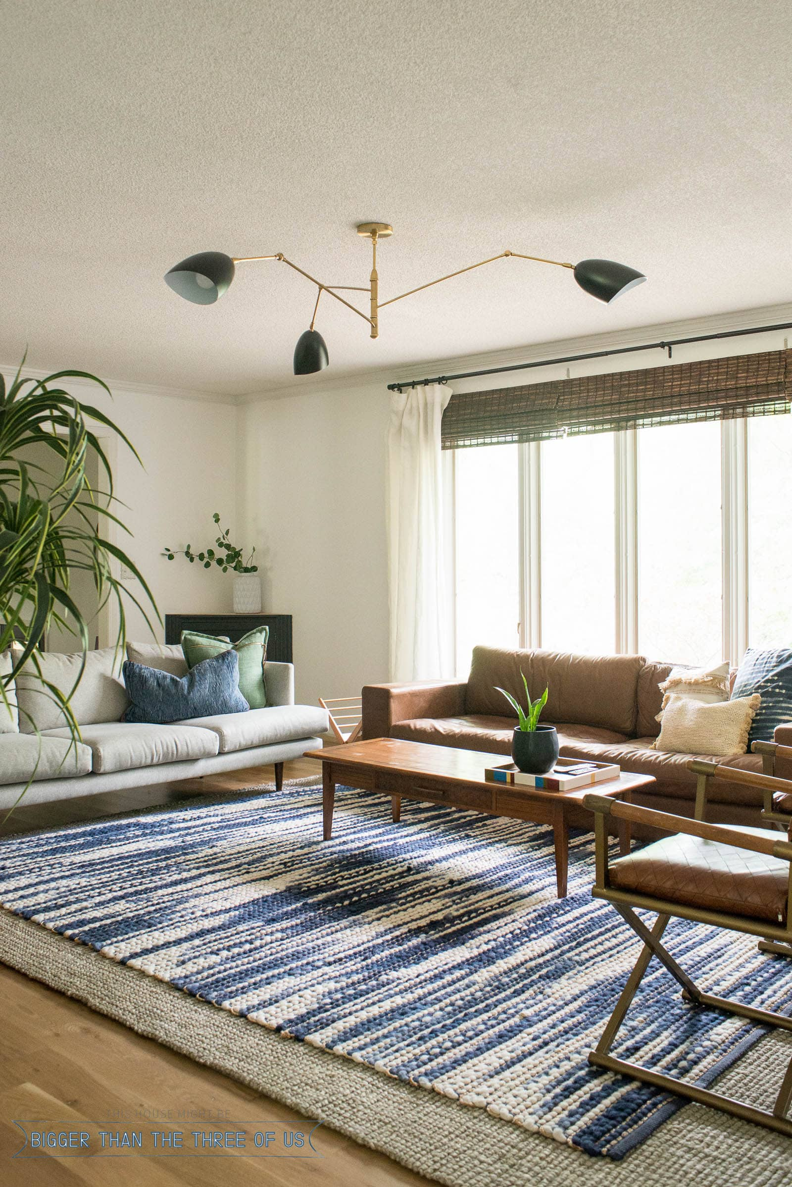 New Black and Brass light for the living room. Blue and white rug, leather couch in living room.