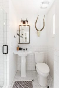 All white powder bathroom with unique art