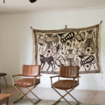 Oversized vintage textile on wall in living room.