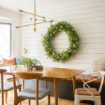 Christmas Decor in Dining room showing an oversized wreath on a shiplap wall with a built-in bench with leather cushion.