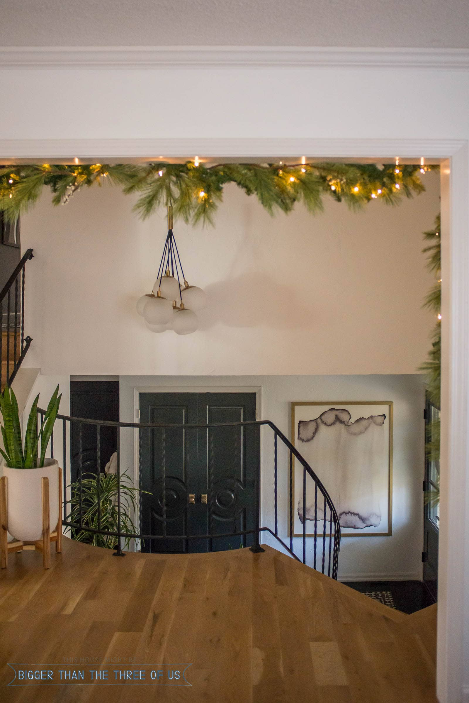 Christmas Garland hanging in doorway overlooking entryway with blue and brass accents.