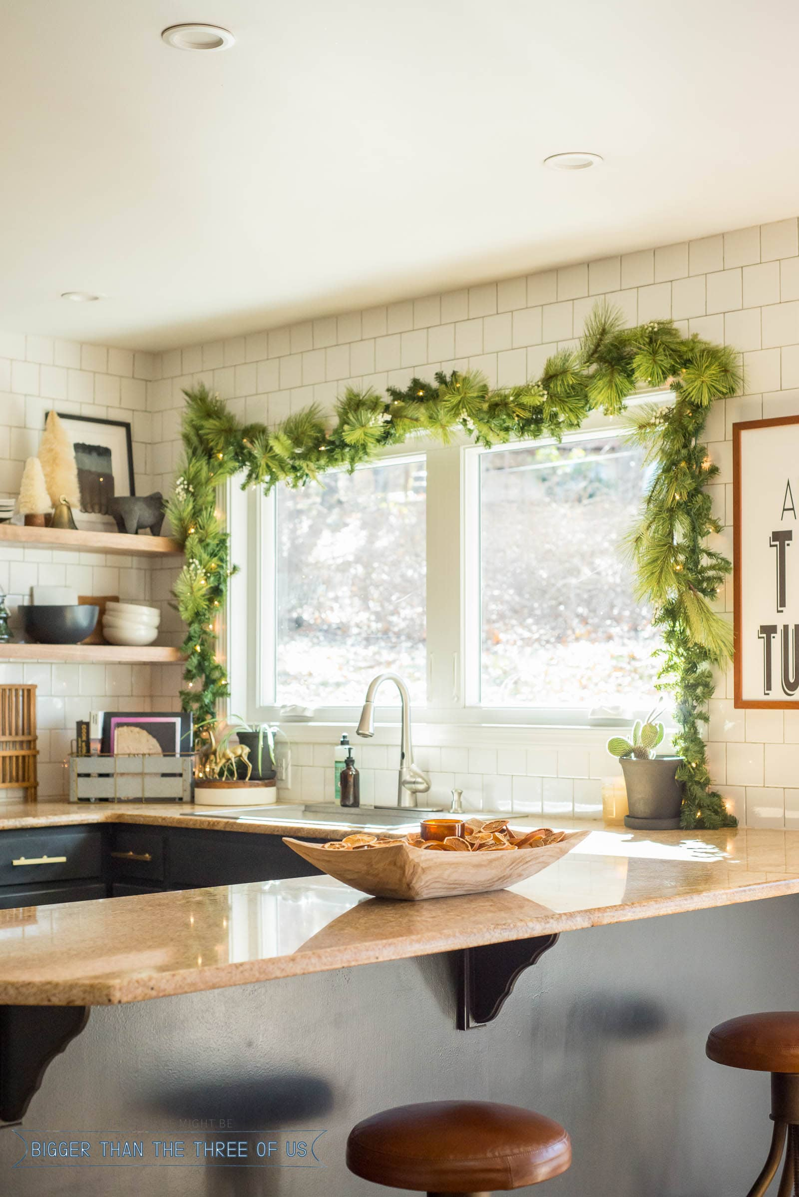 Christmas Swag over kitchen windows with dried oranges in a bowl on granite countertop