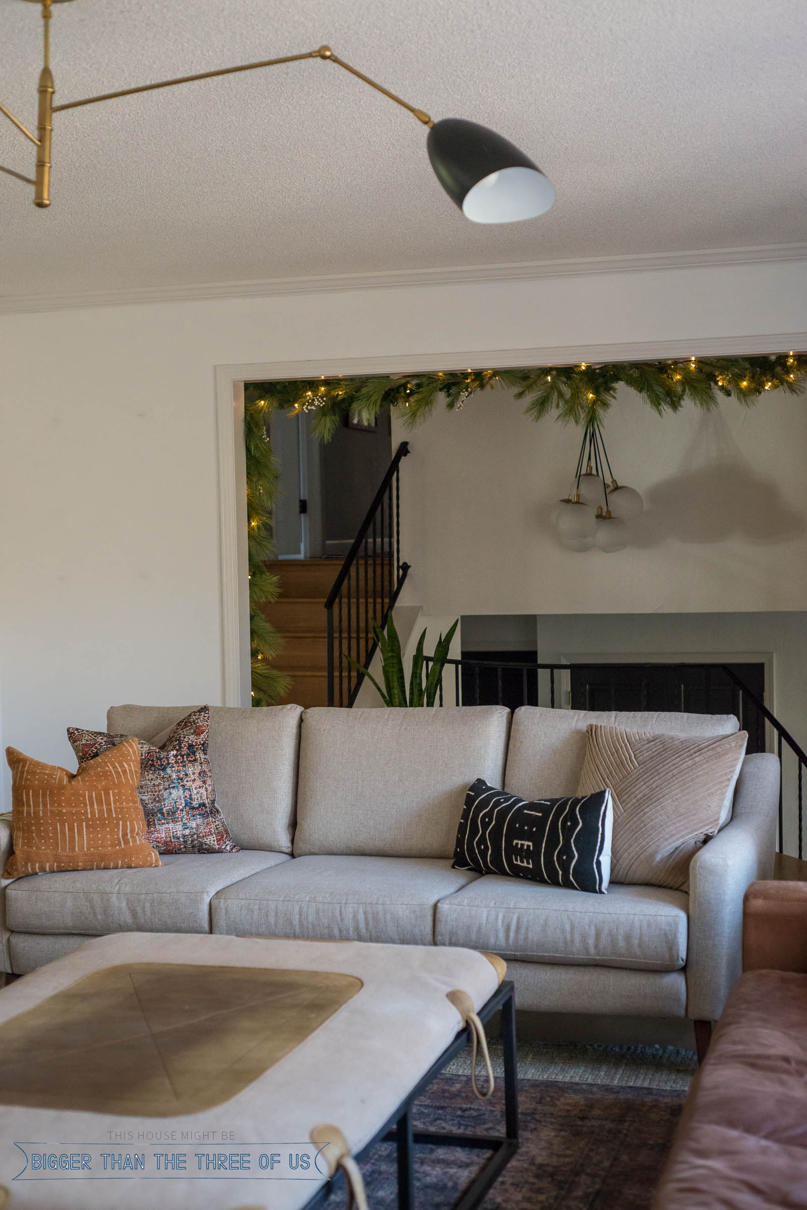 Gray couch in living room with garland strung over doorway behind it.