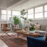 White painted brick sunroom with tile floor and an eclectic boho seating area with campaign leather chairs.