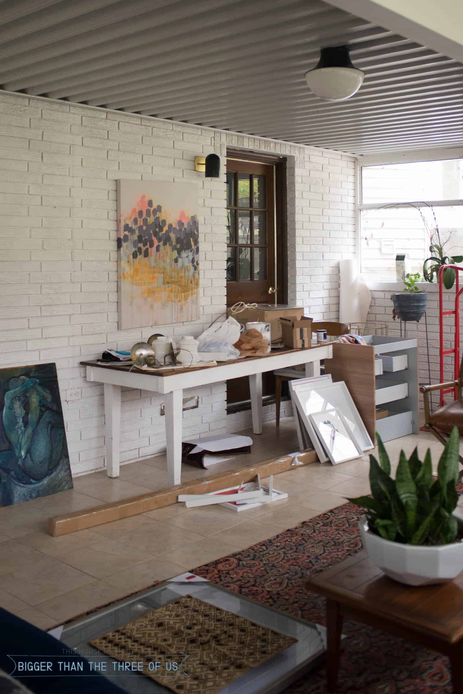 Wall in sunroom with projects supplies on table