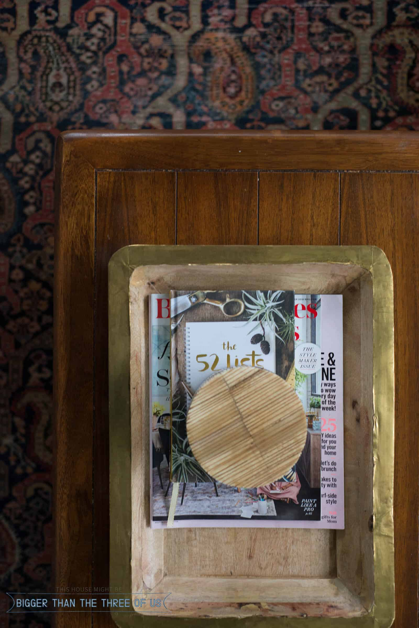 Coffee table with wood tray styled with magazines and a wood box.