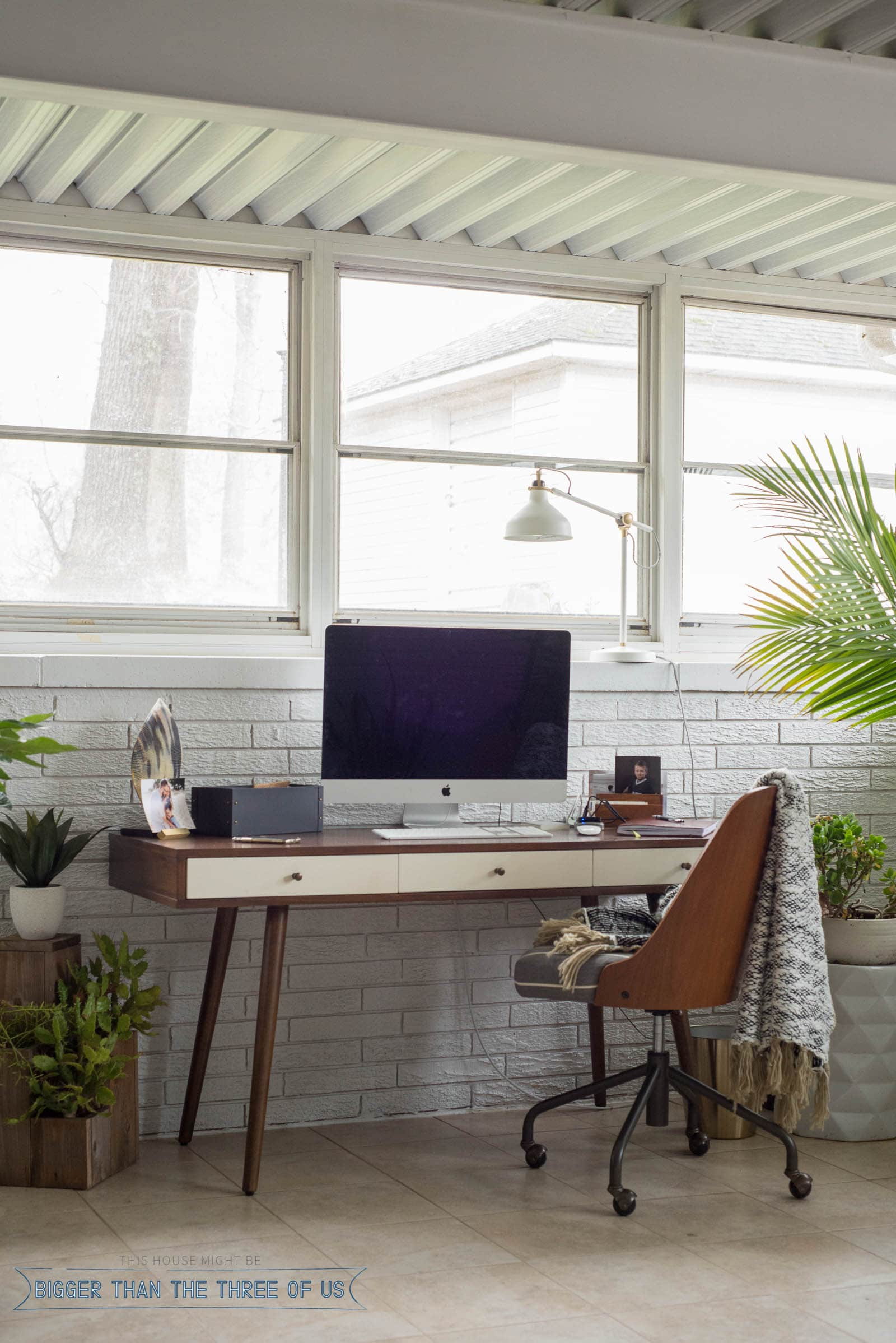 Mid Century Modern Walnut Desk In Sunroom With Plants