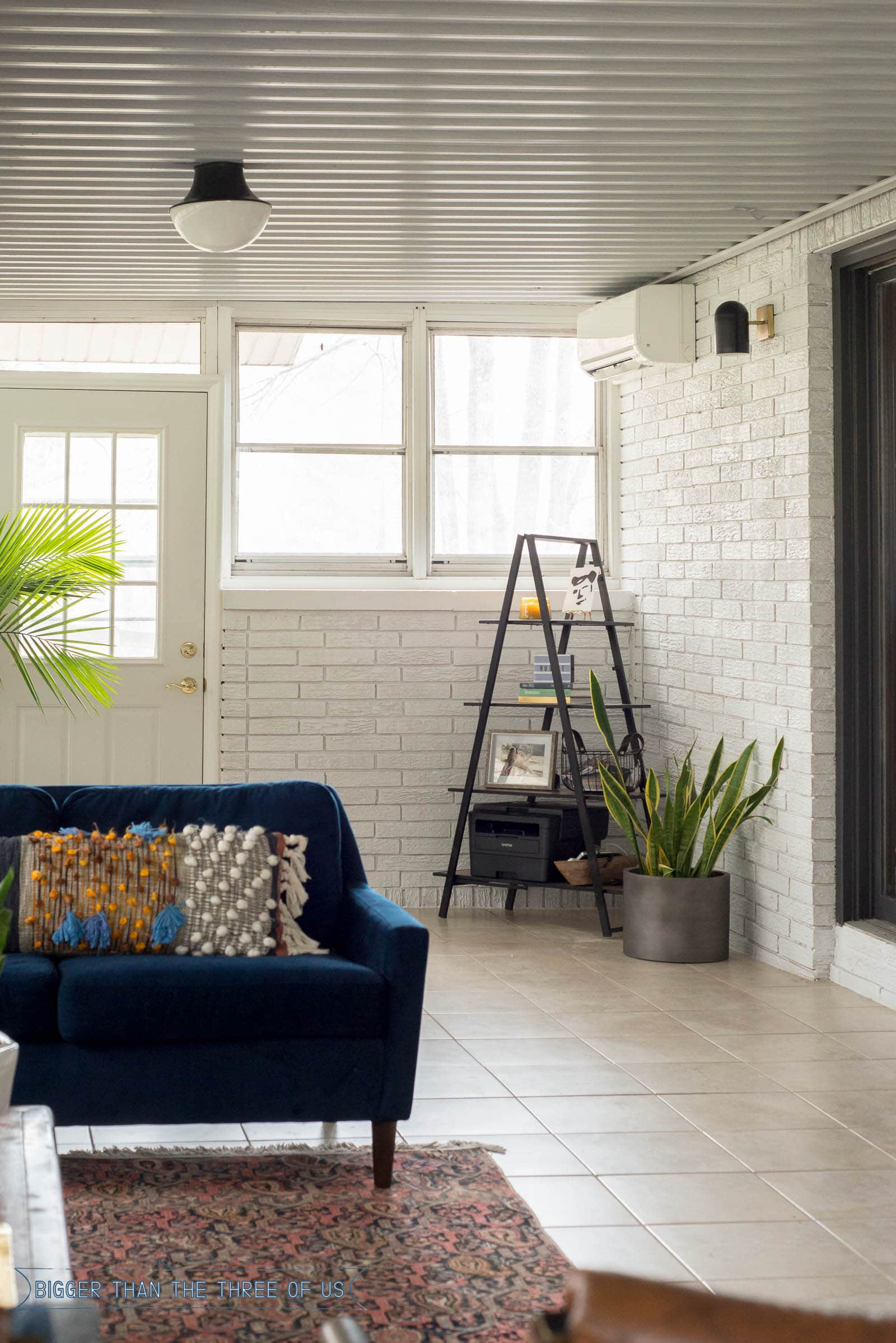 A frame shelf in the corner of a white painted sunroom with plants around it.