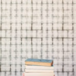 A stack of books in front of wallpaper