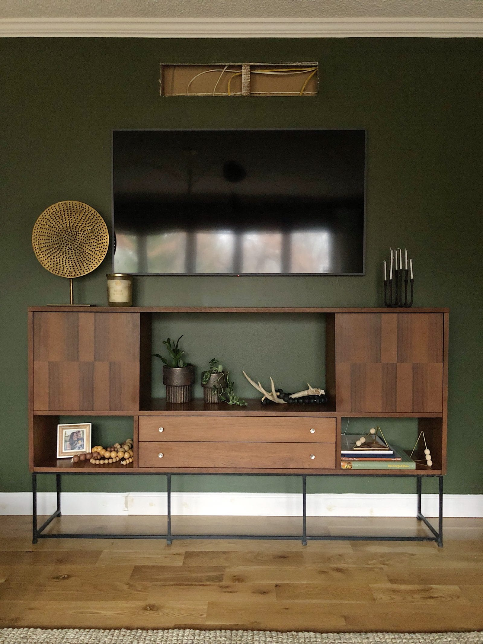 Mid Century Buffet as TV Console in front of a green wall and what it means to show hospitality.