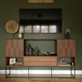 Mid Century Buffet as TV Console in front of a green wall.