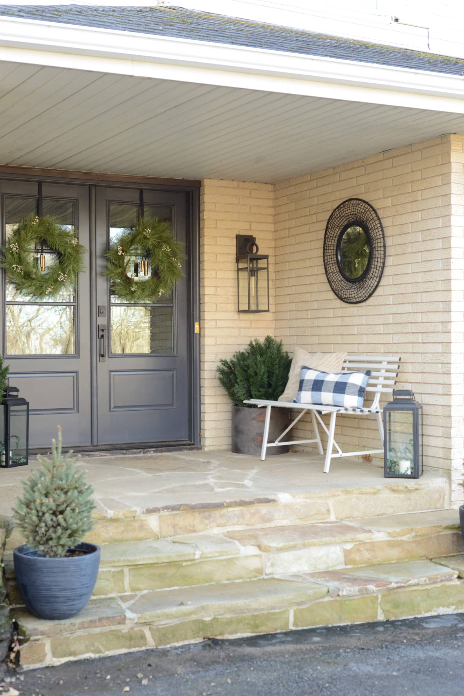 Double front doors on the front porch with white bench styled for winter.