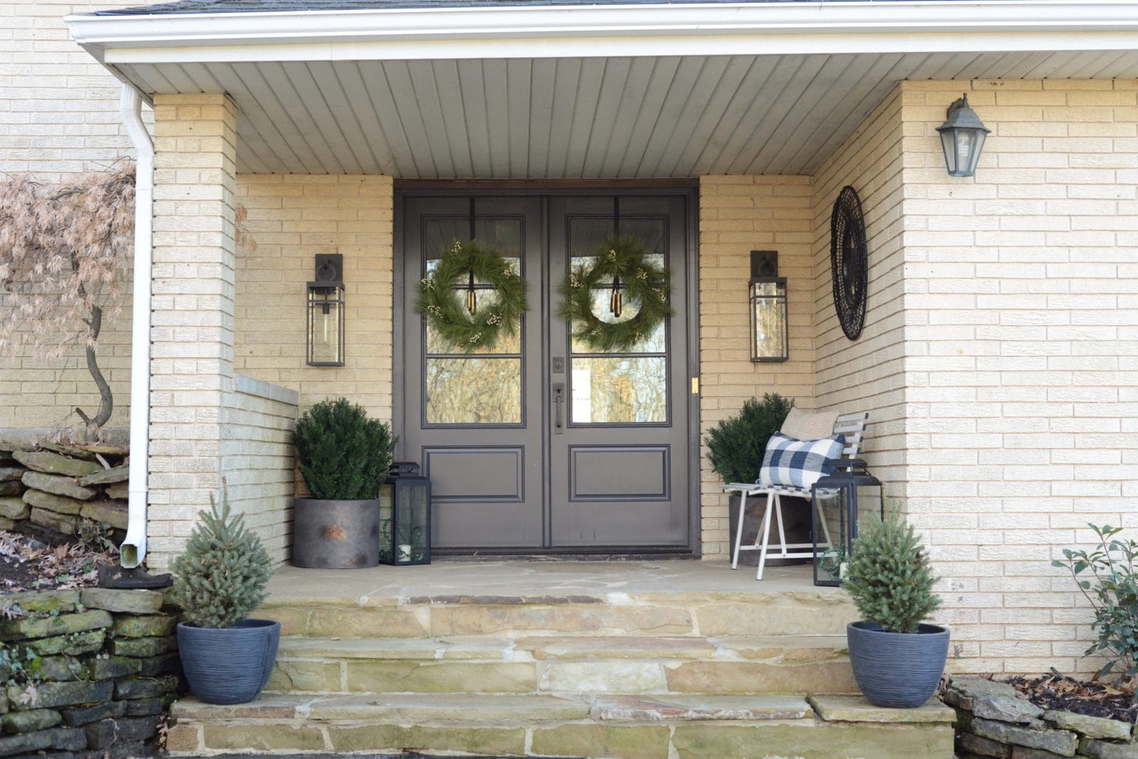 Front porch view with stone floor, black front doors and wreaths