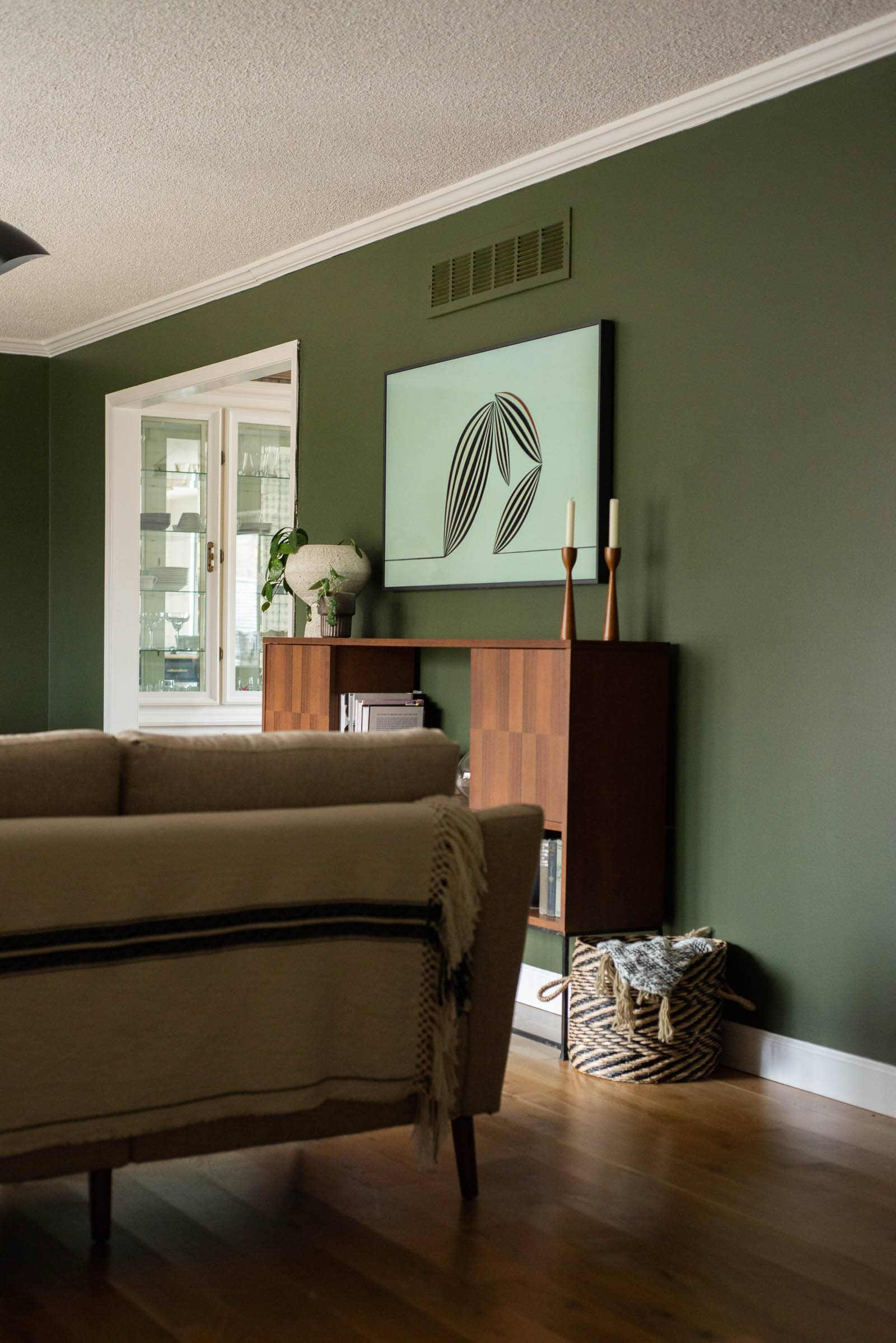 Green wall with a vintage media cabinet on it and a tv above.
