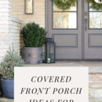 The front porch with two planters and double glass front doors