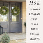 The Front porch decorated with wreaths and a shrub. Cream brick and Cracked Pepper door paint.