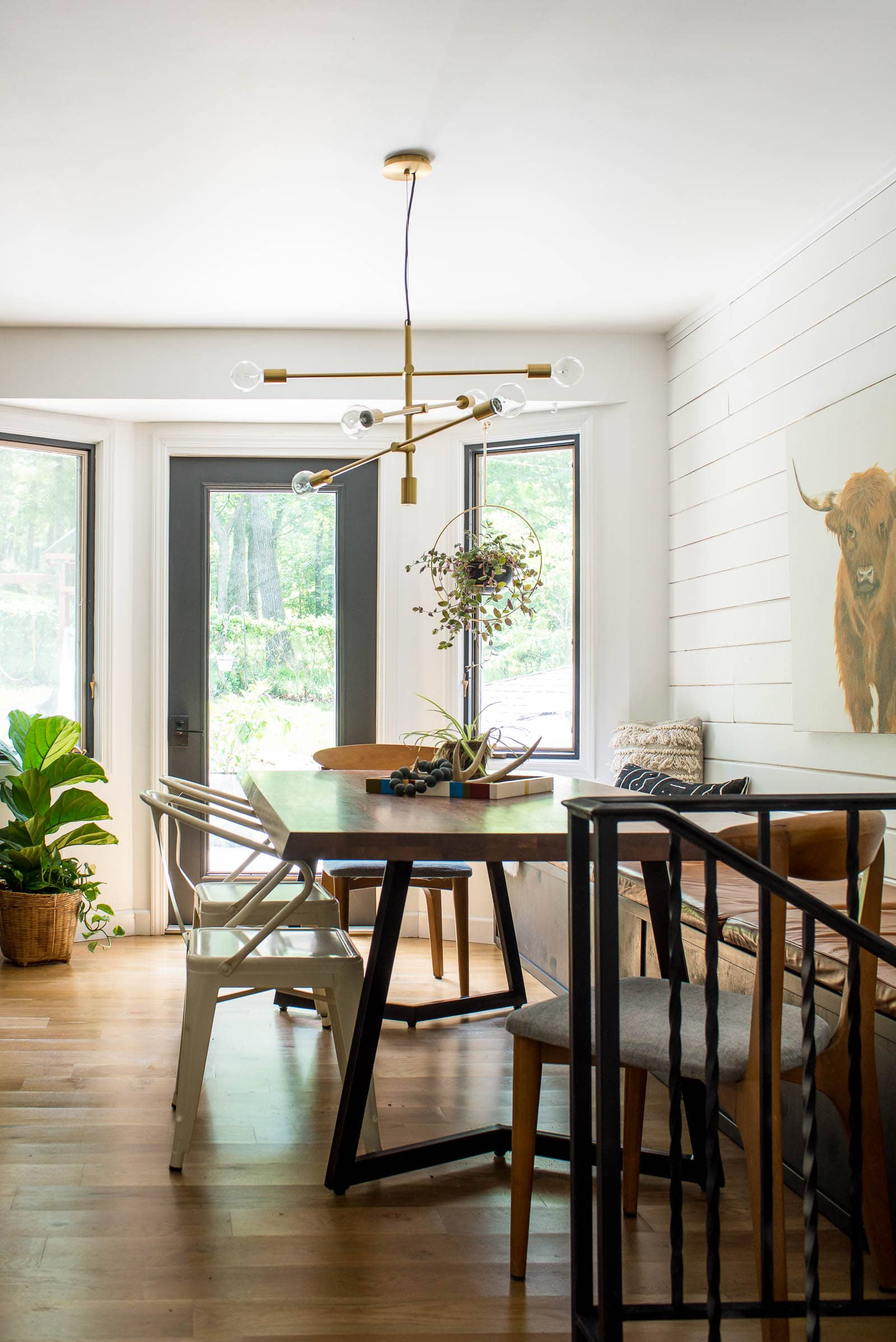 Eclectic eating space with shiplap, wood floors and a dining room table